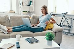 Beautiful young woman. Smiling and using laptop while resting on the sofa at home stock photo