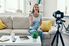 Beautiful young woman. Smiling and waving while making social media video at home stock images