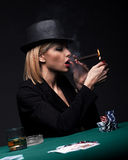 Beautiful young woman smokes a cigar during a poker game Royalty Free Stock Images