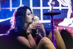 Beautiful young woman smokes hookah in a bar with make-up. And fashionably dressed Royalty Free Stock Image