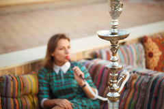 Beautiful young woman smokes a hookah in a cafe Royalty Free Stock Photos