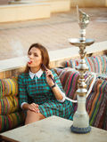 Beautiful young woman smokes a hookah in a cafe Stock Images