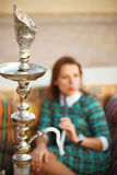 Beautiful young woman smokes a hookah in a cafe Royalty Free Stock Images