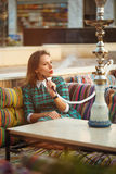 Beautiful young woman smokes a hookah in a cafe Stock Photo