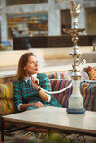 Beautiful young woman smokes a hookah in a cafe Royalty Free Stock Photo