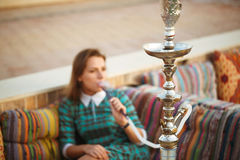 Beautiful young woman smokes a hookah in a cafe Royalty Free Stock Image
