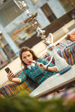 Beautiful young woman smokes a hookah and makes selfie in a cafe Royalty Free Stock Image