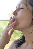 Beautiful young woman smoking cigarette Royalty Free Stock Photos