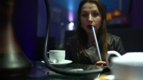Beautiful young woman smoking a hookah and drinking tea stock video