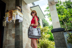 Beautiful young woman with snakeskin python leather handbag posing in sunglasses. Tropical Bali island, Indonesia. Beautiful young woman with snakeskin python royalty free stock photos