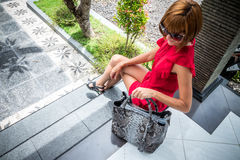 Beautiful young woman with snakeskin python leather handbag posing in sunglasses. Tropical Bali island, Indonesia. Royalty Free Stock Photography