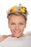 Beautiful young woman in soapsuds and ducks Stock Photo