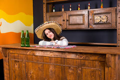 Beautiful young woman in a sombrero leaned on bar counter in Mex. Beautiful young woman in a sombrero leaned on bar counter with beer bottles in Mexican pub royalty free stock image