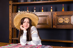 Beautiful young woman in a sombrero leaned on bar counter in a p. Beautiful young woman in a sombrero leaned on bar counter in Mexican pub, a shelf with spicy royalty free stock photo