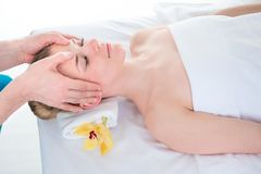 Beautiful young woman in a spa having a relaxing head massage fr. Om a therapist Royalty Free Stock Images