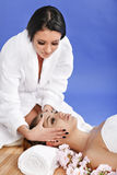 Beautiful young woman in spa salon getting massage, on blue back Royalty Free Stock Photo