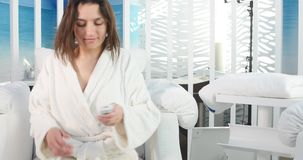 Beautiful young woman in spa salon with remote control stock video footage
