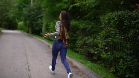 Young woman is talking on the phone on the run, she is in a hurry. outdoors in summer. slow-motion stock footage