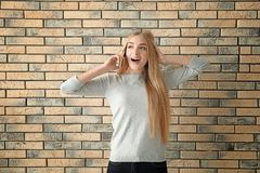 Beautiful young woman speaking by mobile phone. Near brick wall Royalty Free Stock Photography