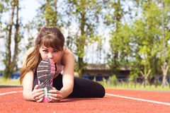 Beautiful Young Woman in Sports Bra Stretching Hamstring on Trac Royalty Free Stock Photos