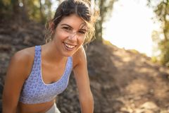 Beautiful young woman in sportswear relaxing after trail run training. Female trail runner taking break after running workout on royalty free stock photography