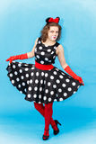 Beautiful young woman in spotted dress dancing in studio Stock Image