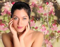 Beautiful young woman with spring flower background. Beautiful brunette woman over pink apple blossom flower background Royalty Free Stock Photo