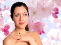 Beautiful young woman with spring flower background. Beautiful brunette woman over pink apple blossom flower background Stock Photo
