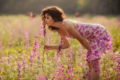 Beautiful young woman in spring flowers outdoors. Beautiful young woman relaxing in purple spring flowers outdoors Royalty Free Stock Photos