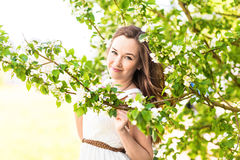 Beautiful young woman in the spring garden among apple blossom, soft focus Royalty Free Stock Image