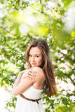 Beautiful young woman in the spring garden among apple blossom, soft focus Royalty Free Stock Photos