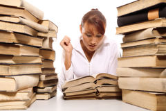 Beautiful young woman with stack of books. On white background royalty free stock image