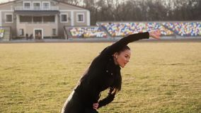 Beautiful young woman at the stadium performs different fitness exercises. stock video