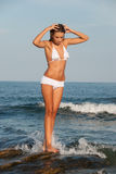 Beautiful young woman stand on sea rocks wear bikini Royalty Free Stock Photography
