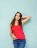 Beautiful young woman standing against blue background with hand in hair Royalty Free Stock Photo