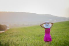 Beautiful young woman standing back countryside, rustick nature place in green field with blue sky copy space.  royalty free stock images