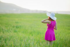 Beautiful young woman standing back countryside, rustick nature place in green field with blue sky copy space.  stock image