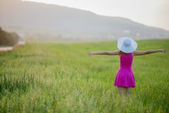 Beautiful young woman standing back countryside, rustick nature place in green field with blue sky copy space.  stock photos