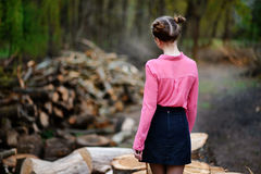 Beautiful young woman standing back to camera on stack of felled tree trunks in the forest. Beautiful young woman sitting on stack of felled tree trunks in the Stock Photo