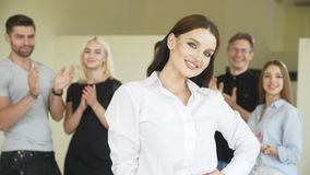 A beautiful young woman is standing in backdrop of coworkers row They are clapping