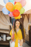 Beautiful young woman standing with balloons at wooden plank bed near pool Royalty Free Stock Photos