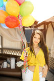 Beautiful young woman standing with balloons at wooden plank bed near pool Stock Image