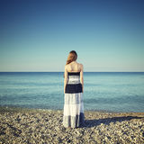 Beautiful young woman standing on the beach Stock Image
