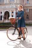 Beautiful young woman standing with bicycle in the city royalty free stock photography