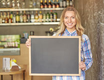 Beautiful young woman standing with a blackboard at the cafe. Copy space Royalty Free Stock Image