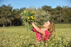 Beautiful young woman standing in blooming meadow Stock Photo