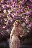 Beautiful young woman standing at blossoming tree in the garden Royalty Free Stock Photos