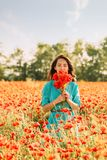 Beautiful woman standing in poppies meadow. Beautiful young woman standing with bouquet of red poppies in meadow on summer day royalty free stock photo