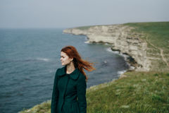 Beautiful young woman standing on a cliff of a mountain near the sea.  stock photography