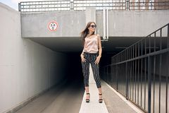 Beautiful young woman standing at the entrance to the underground garage. The model wears stylish clothes, a beige. Jersey, and black breeches in a white stripe Royalty Free Stock Photography